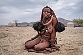 Portrait of a Himba woman sitting on the ground in a small village. Himbas are a bantu tribe who migrated into what today is Namibia a few centuries ago. They presumably come from East Africa and especially the women keep very complicated ways of dressing