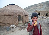 Wakhi nomad boy eating bread in front of his yurt, Big pamir, Wakhan, Afghanistan.