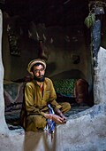 Afghan man inside his traditional pamiri house, Badakhshan province, Khandood, Afghanistan.