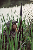 Side view of hunter sitting amidst grass at lakeshore
