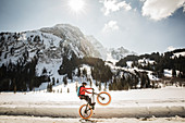 A young man performs a wheelie on a fatbike, snowbike, mountainbike  at Lauenensee near Gstaad, Bernese Oberland, Switzerland
