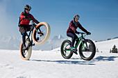 Ein junger Mann und eine junge Frau auf Fatbikes, Snowbikes, Mountainbikes bei Sparenmoos oberhalb von Gstaad, Berner Oberland, Schweiz