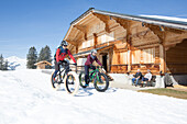 A young man and a woman on fatbike, snowbike, mountainbike at Sparenmoos above Gstaad, Bernese Oberland, Switzerland