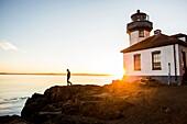 Silhouette of Caucasian man walking on rocks near lighthouse