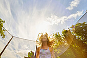 Low angle view of Caucasian girl jumping on trampoline