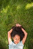 Smiling Hispanic girl laying in grass