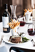 Gourmet pepper steak with french fries and red wine