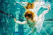 Caucasian woman wearing dress swimming underwater