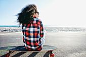 Hispanic woman sitting on skateboard at beach