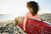 Hispanic woman holding surfboard at beach