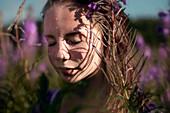 Pensive Caucasian girl sweating near wildflowers