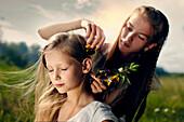 Caucasian girl placing flower in hair of sister