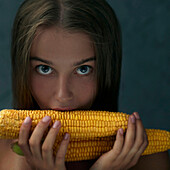 Caucasian girl eating corn on cob