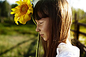 Profile of Caucasian girl with freckles holding sunflower