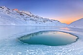 Soft colors of a cold dawn reflected in a pool of turquoise water surrounded by the snow in the middle of White Lake, Bernina Pass, Canton of Graubuenden, Engadine, Switzerland, Europe