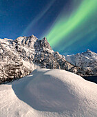 Northern Lights illuminate the snowy peaks and the blue sky during a starry night Budalen Svolvaer Lofoten Islands Norway Europe