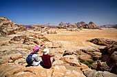Jordan. Wadi Rum desert. protected area inscribed on UNESCO World Heritage list. Tourist and local Bedouin guide seated on a rock, contemplating the landscape from mount Jebel Burdah