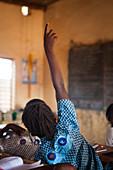 Burkina Faso, Ouagadougou, Girl seen from behind raising her hand in class