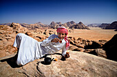 Jordan. Wadi Rum desert. protected area inscribed on UNESCO World Heritage list. Bedouin having a tea break at the top of mount Jebel Burdah