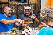 ' Hikers having Zirbenschnaps, Alpine hut ''Wia dahoam Huettn'', Leistalm, Totes Gebirge, Styria, Austria, Europe'