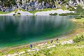 Hikers at Lake Schwarzensee, Tauplitzalm, Totes Gebirge, Styria, Austria, Europe