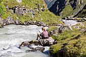 A woman reading at Falkenoner Gletscherbach at the New Regensburger alpine Hut, Stubaier Hoehenweg, Stubaital, Tyrol, Austria, Europe