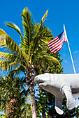 Typical Florida with manatee figure, American flag and palm trees, Fort Myers Beach, Florida, USA