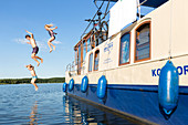 Family jumps from a boat into the water, swimming fun with a family, houseboat tour, Lake Mirower See, Kuhnle-Tours, Mecklenburg lakes, Mecklenburg lake district, MR, Mirow, Mecklenburg-West Pomerania, Germany, Europe