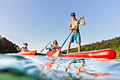 Stand up paddling on lake, boy with paddle, red SUP, girls in red boat, canoe, kayak, water sports, crystal clear green water, lake Schmaler Luzin, holiday, summer, swimming, MR, Feldberg, Mecklenburg lakes, Mecklenburg lake district, Mecklenburg-West Pom