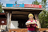 A girl with hamburger with reindeermeat from Lap Danalds. At Ladtjojaure, Lapland, Sweden.