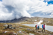 A woman and two girls are hiking on the Kungsleden trek, in the wildernes. From Kebnekaise Fjällstation to Singistugorna. Lapland, Sweden.