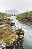 Zwei Mädchen und eine Frau auf einer Hängebrücke unterwegs zur Kaitumjaurestugorna. Kungsleden Trekking, Laponia, Lappland, Schweden.