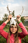 A girl shows the scull of a reindeer. Kungsleden trekking, Laponia, Lapland, Sweden.