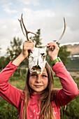 Ein Mädchen zeigt einen Schädel eines Rentiers. Kungsleden Trekking, Laponia, Lappland, Schweden.
