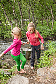 Two girls carry water from the crekke at Teusajaurestugorna. Kungsleden Trekking, Laponia, Lappland, Schweden.