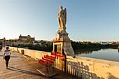 Frau, Skulptur des Erzengels Raphael, Schutzpatron von Cordoba, 17.Jhd, Puente Romano, Brücke, historisches Stadtzentrum von Cordoba, UNESCO Welterbe, Rio Guadalquivir, Fluss, Cordoba, Andalusien, Spanien, Europa