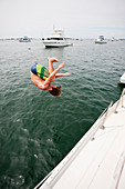 A Man Jumping Into The Water Of Great Salt Pond In New Harbor Of Block Island