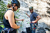 A Man Belaying Does A Safety Check And Demonstrates To The Climber Before Beginning A Climb In Utah's Little Cottonwood Canyon
