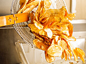 Feshly-Fried Potato Chips Being Poured Out Of A Fryer Basket
