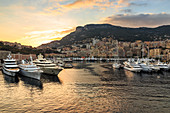Vivid sunset over super yachts, glamorous harbour of Monaco (Port Hercules), from the sea, Monte Carlo, Monaco, Cote d'Azur, Mediterranean, Europe