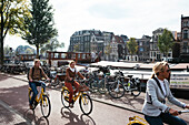 Young women riding bicycle in the Center along the Canal, Amsterdam, Netherlands, Europe