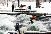 Surfing the Eisbach during Snowfall in English Garden, Munich, Germany