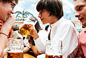 Young man in traditional cloth drinking beer in beer tent at Oktoberfest, Munich, Bavaria, Germany