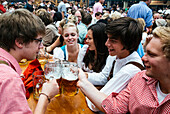 Revelers raise their beer mugs to toast at Oktoberfest, Munich, Bavaria, Germany