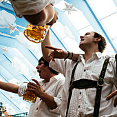 Young men in leather trousers standing on beer benches celebrate Oktoberfest in the beer tent