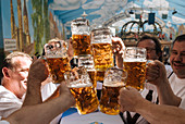 Raising beer mugs at Octoberfest, Munich, Bavaria, Germany