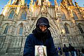 A homeless woman begs for money with a cup and a picture of Jesus in front of the Cathedral De Barcelona in Barcelona, Spain.