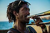 Afro Cuban man with dreadlocked hair plays trombone for tourist on the Malec??n (Avenida de Maceo), the seawall and promenade along the coast of Havana, La Habana, Cuba.
