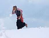 A woman porter is being hit by a snowball thrown by a fellow porter. The inhabitants of the village of Sama Goan are offering their services to expeditions on Manaslu bu carrying gear to basecamp.    The Manaslu mountain in the Nepal Himalayas is 8163 met