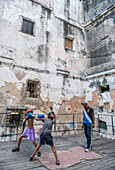 Two boys sparring on the makeshift ring at Project Cuba Boxeo, an aid project from Malaika Aid for Children, the creation of Samuel 'Sammy' Fabbri, who is seen coaching in this photo. The organization brings boxing to Cuban children from 8-21 years of age